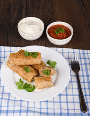 Pancake rolls with meat filling, served with fresh parsley