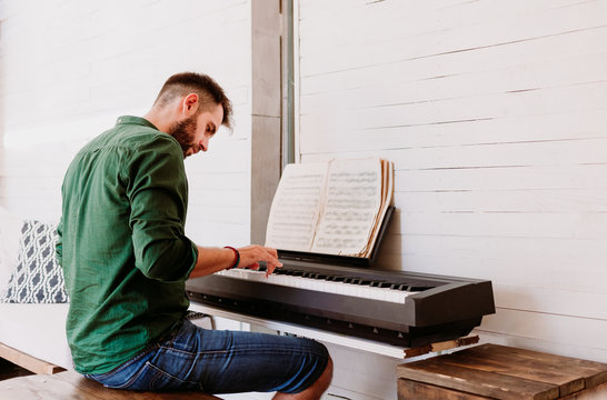 Young man playing electric piano at home studio