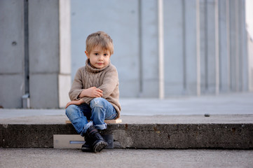 A four-year-old white blond pensive  boy with a lovely eyes looking straight ahead