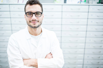 Portrait of smiling pharmacist at cabinet in pharmacy