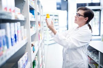 Pharmacist holding product at shelf in pharmacy