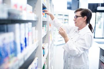 Pharmacist sorting medicine at shelf in pharmacy
