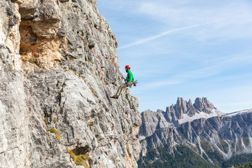 Italy, Cortina d'Ampezzo, man abseiling in the Dolomites mountains