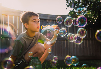 Boy blowing soap bubbles while crouching in backyard