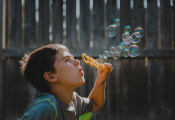 Close-up of cute boy blowing bubbles at backyard during sunny day