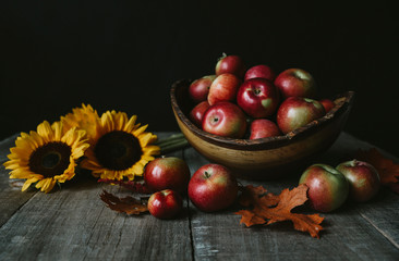 Close-up of fresh apples with sunflowers and leaves on wooden table against black background