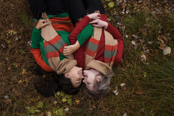 High angle view of smiling female friends wearing warm clothing lying on field in forest
