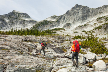 Male hikers climbing mountain against sky