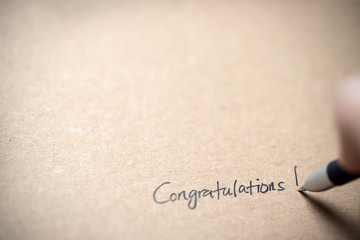 Hand writing congratulations on piece of old grunge paper
