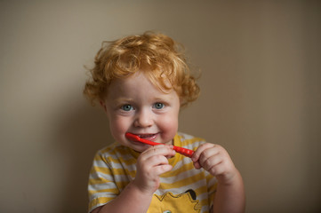 Portrait of baby boy brushing teeth against wall at home