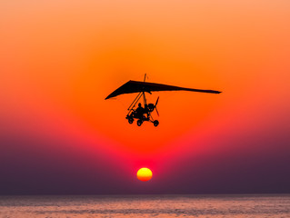 Motorized glider flies against the sunset over the sea.