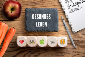 """Wüfel mit Symbolen und Schiefertafel mit der Aufschrift """"gesundes Leben"""""""