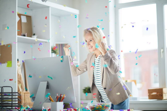 Portrait of excited mature woman celebrating success in office and looking at computer screen with confetti falling overhead, copy space