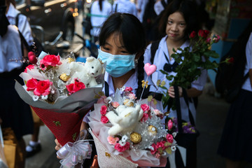 Students hold up flower bouquets on Valentine's day in Bangkok