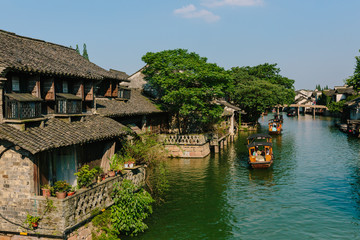 Traditional Chinese houses by water with boats, in the old town of Wuzhen, China