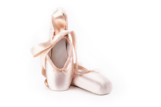 Pointe shoes ballet dance shoes with a bow of ribbons beautifully folded on a white background with a lot of light.