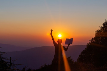 Fototapeta human praying to the GOD while holding a crucifix symbol with bright sunbeam on mountain at sunset time