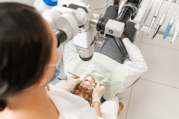 Focus on patient. Young woman dentist treating root canals using microscope in the dental clinic. Man patient lying on dentist chair with open mouth.