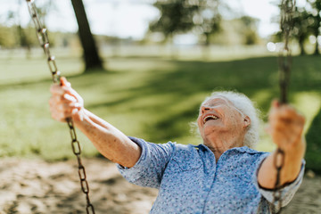 Cheerful senior woman on a swing at a playground Fototapete