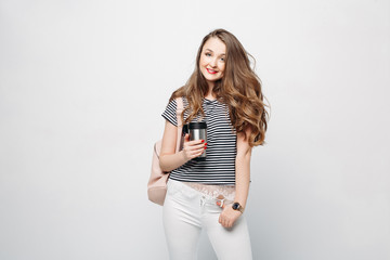 Pretty and stylish brunette girl with red lips, long wavy hair after beauty salon and shopping, posing at studio, holding thermos with warm coffee or tea. Sensuality fashionable woman looking down.