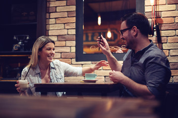 Loving couple sitting in a cafe enjoying in coffee and conversation