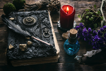 Spell book, magic potion and other various witchcraft accessories on the wizard table background. Fotoväggar