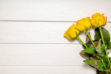 A bouquet of yellow roses lies on a whitewooden background