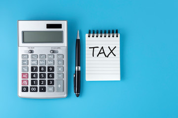 Tax word on notepad with calculator