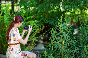 Young Woman Photographer Taking Images In A Garden