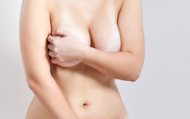 Naked beauty. Cropped photo of beautiful young shirtless woman covering big breast by her hands