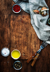 Food cooking background, vertical template. Serving, cutting board on rustic wooden table background, forks, spices, salt, olive oil, napkin. View from above