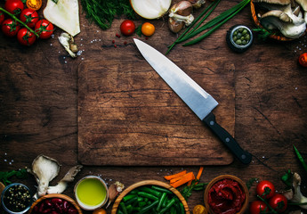 Food cooking background, ingredients for preparation vegan dishes, vegetables, roots, spices, mushrooms and herbs. Big kitchen chef knife. Healthy food concept.