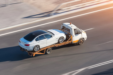 Recovery truck to transport a car on the highway in the city