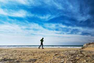 Man athlete runs along the seashore on a sunny day. Trail Running