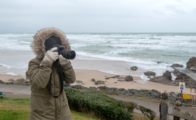 woman photographer taking a picture at seaside in winter