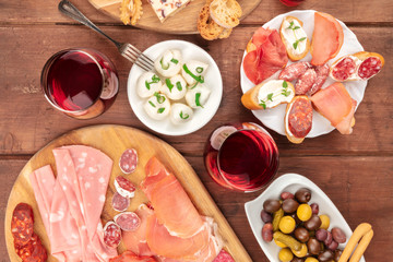 Wine, cheese and charcuterie tasting and pairing. An overhead photo of glasses of wine with cold cuts, sandwiches and olives
