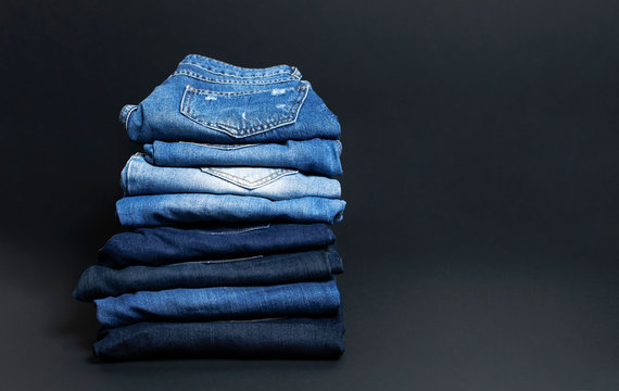 Stack of various blue jeans on black background. Beauty and fashion, clothing concept. Detail of nice blue jeans. Jeans texture or denim background. Collection of jeans.