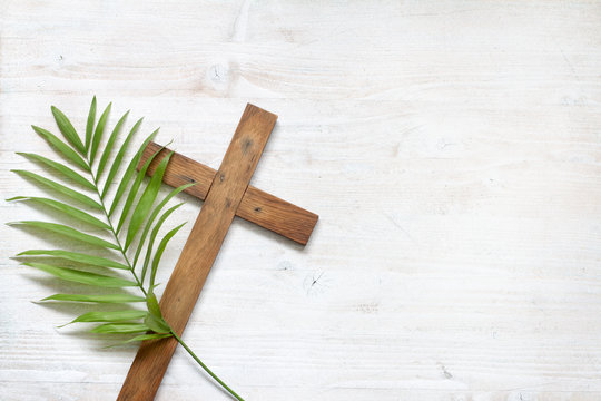 Cross and palm on wooden white background easter sign symbol concept
