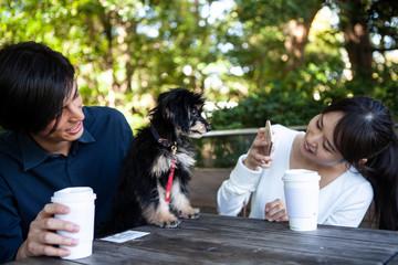 可愛い飼い犬を写真に収める女性