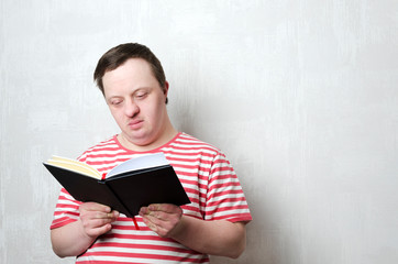 Young man with down syndrome reading a book