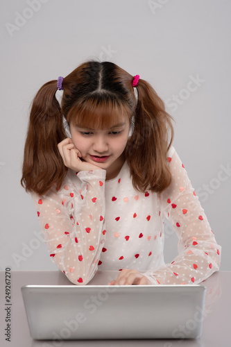 Beautiful asian student girl look at laptop while doing homework