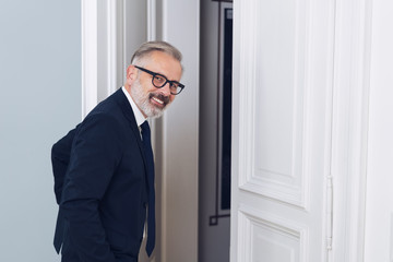 Smiling mature businessman leaving the room