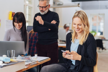 Blond woman using smartphone and smiling in office
