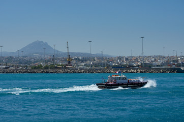 Pilot boat sailing on the azure sea in the Harbor of Heraklion on the background of the mountain top and the city (Greece)