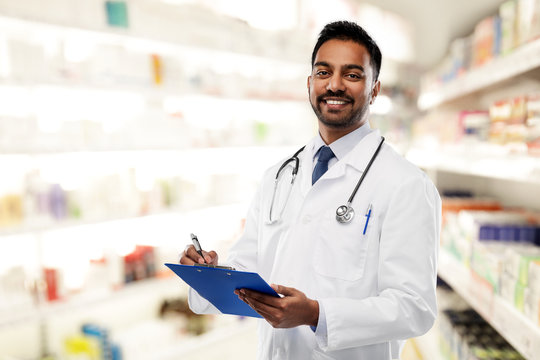 medicine, pharmacy and healthcare concept - smiling indian male doctor or pharmacist in white coat with stethoscope and clipboard over drugstore background