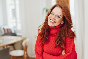 Red-haired girl in red sweater winking
