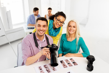 photography, model agency and creative people concept - photographers with camera at photo studio