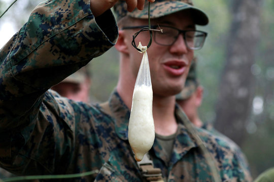 A soldier presents rice cooked in a condom during the Cobra Gold multilateral military exercise in Chanthaburi