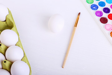 White eggs, paints and tassels, preparation for coloring for Easter.