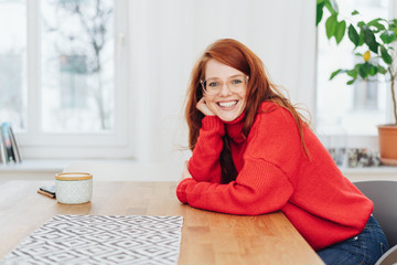 Smiling young woman looking down a table